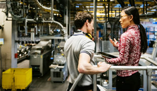Mechanic And Female Engineer Talking in Factory